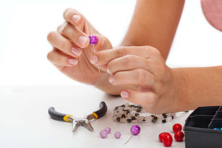 colorful beads: A person making earings from colorful beads and needles