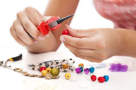 A person designing colorful earings with plactic beads Stock Photo