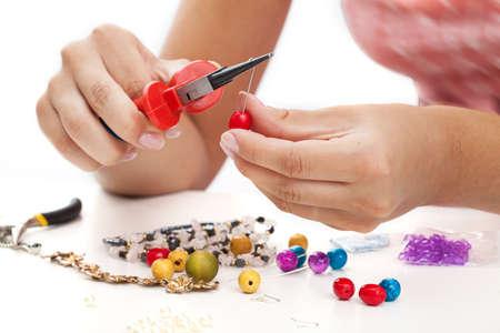 Een persoon ontwerpen kleurrijke oorbellen met plactic kralen Stockfoto