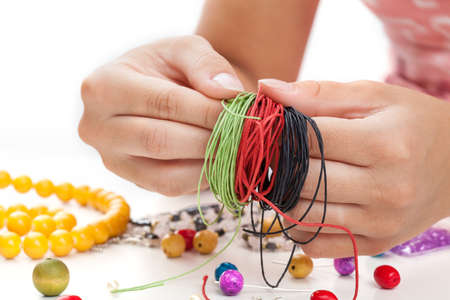 bead jewelry: Green red and black thongs wrapped around someones fingers