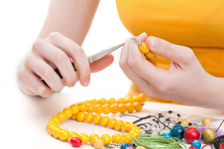 bead jewelry: A woman making a wooden yellow bead necklace Stock Photo