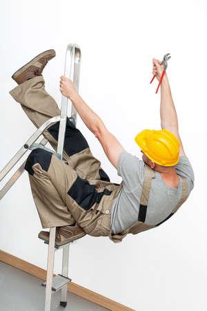 accidente trabajo: Un trabajador con un casco amarillo que cae de una escalera de metal