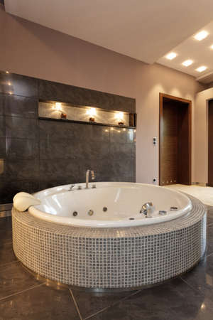 An exclusive round bath with small tiles in an elegant bathroom photo