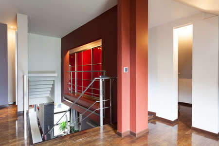 A stairway with a landing with a modern red wall photo