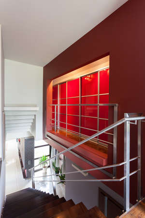 Metal stairs and a red lightened wall photo