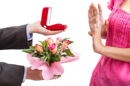 rejected: A man proposing with a ring and flowers and a woman rejecting Stock Photo