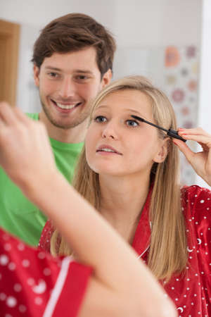 A husband watching his wife apply a mascara photo