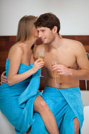 wife of bath: A couple talking over champagne in the bathroom in their towels