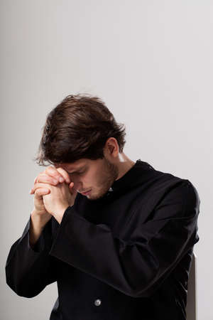 cleric: Catholic priest meditating in  focus with folded hands
