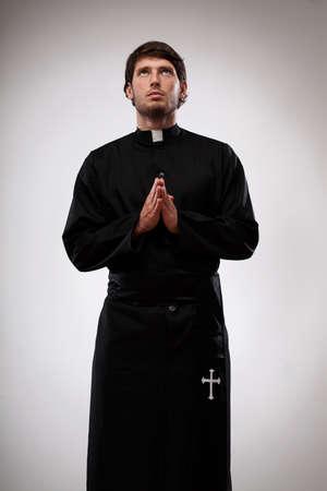 Jonge monnik gekleed in zwarte soutane is nieuwsgierige tot God en dank te zeggen
