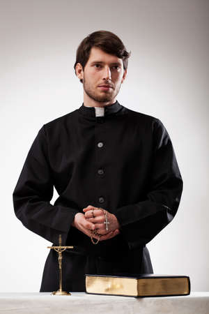 Handsome reverend with crucifix, rosary and the Bible