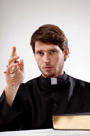 Catholic man with rosary in hand and the Bible Stock Photo
