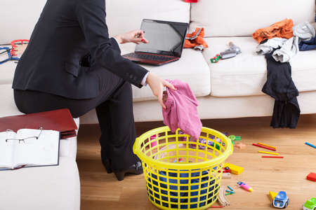 Active businesswoman cleaning house and working on computer in the same time Stock Photo