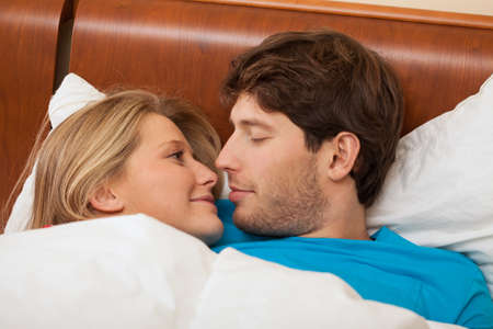 A close up of pretty lovers faces in bed Stock Photo - 24958491