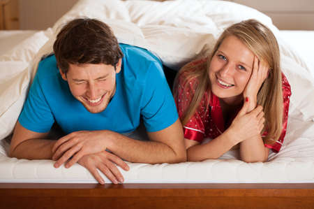 A couple laughing and having fun while lying in bed Stock Photo - 24958482