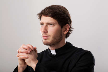clergyman: Clergyman wearing soutane praying with folded hands
