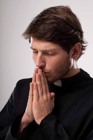 cleric: Vicar praying to God with closed eyes
