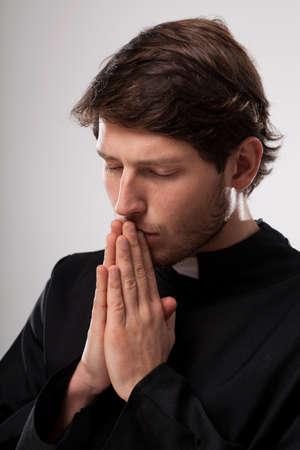 vicar: Vicar praying to God with closed eyes