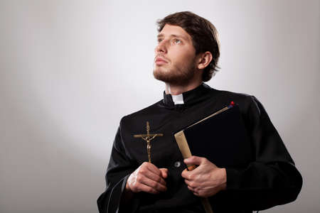 vicar: Vicar holding a holy bible and crucifix