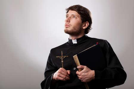 sacerdote: Vicario que sostiene una biblia santa y crucifijo