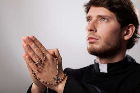 priesthood: Priest praying in focus with a rosary  Stock Photo