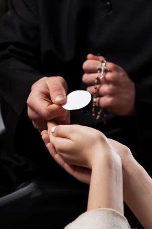 Katholieke priester die de gelovige een heilige communie geeft