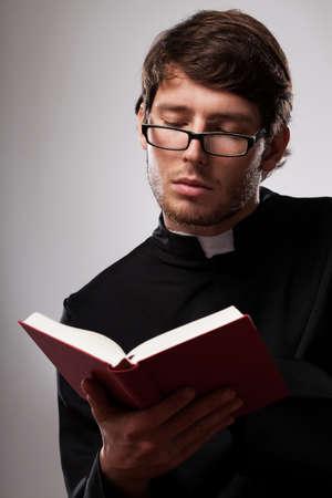 sotana: Vicario joven que llevaba sotana negro de estudiar las Sagradas Escrituras de la Biblia Foto de archivo