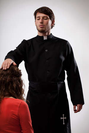 pastor: Priest in black cassock supporting to loose believers sins Stock Photo