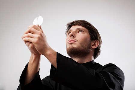 toog: Jonge priester, gekleed in zwarte soutane viert een Heilige Mis met wafer Stockfoto