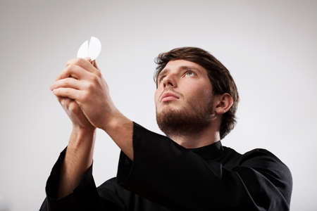cassock: Young priest wearing black cassock is celebrating a Holy Mass with wafer
