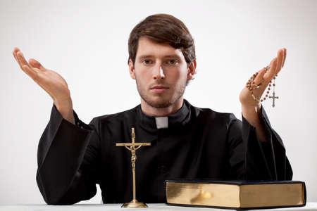 Jonge dominee met kruisbeeld, rozentuin en de Bijbel Stockfoto - 24958435
