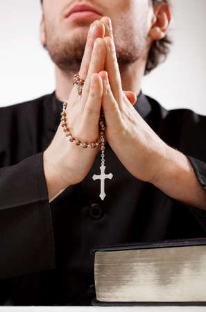 Priest with a rosary concentrated on a prayer photo