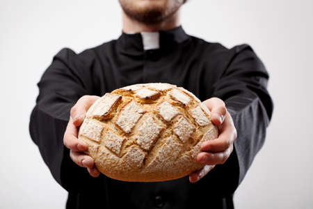 eucharist: Priest holding loaf of bread as an Eucharist
