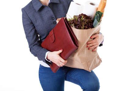 life: Jeune femme multitâche avec la serviette et le sac avec les achats à domicile