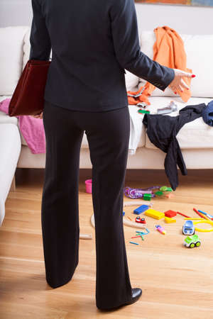 Young active mother back from work and worrying about a mess at home photo