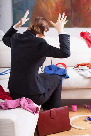 Active businesswoman and mother is frustrated of big mess at home  photo