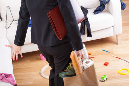 Businesswoman back from work and see terrible mess at home photo