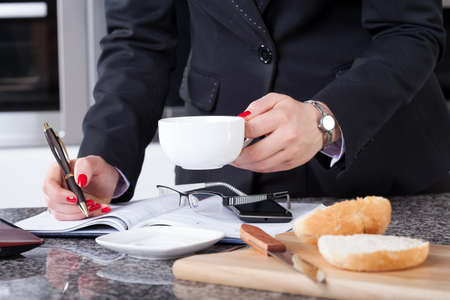 Businesswoman in rush eating breakfast, drinking coffee and working the same time photo