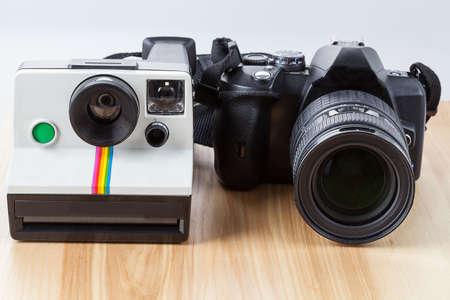 darkroom: A white polaroid camera and a black digital camera