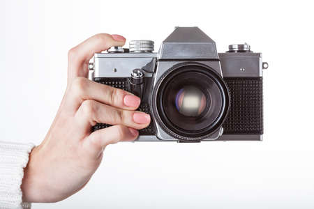 A caucasian hand snapping a photo using a stylish camera photo