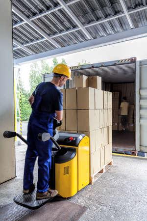 pallet: Exportación de almacén de los artículos en los paquetes que hacen por un trabajador Foto de archivo