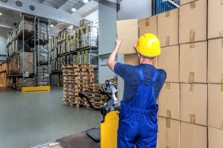 factory workers: Carrying a package by a worker in a warehouse