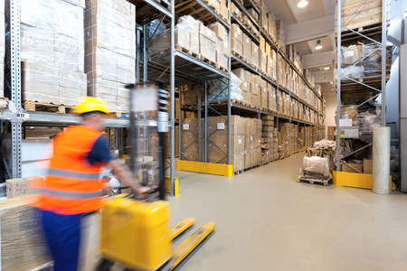 warehouse: Man pushing a yellow forklift in huge store Stock Photo