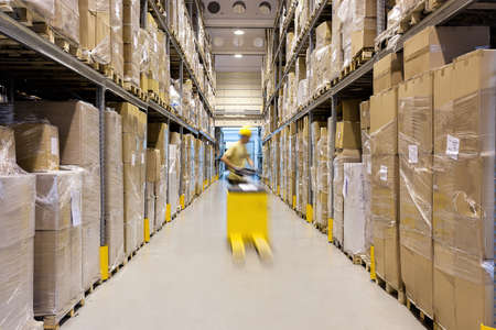 warehouse equipment: Warehouse worker with a yellow hand pallet truck