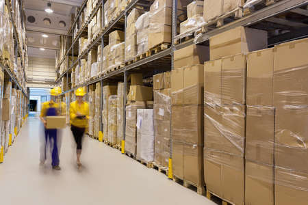 Two workers in warehouse controlling products Stock Photo