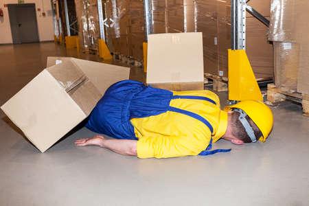 lesionado: Trabajador en sombrero duro golpeado por el cartón en almacén
