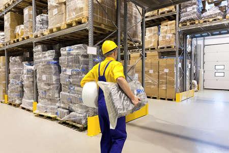 Man in yellow hard hat organizing a warehouse photo