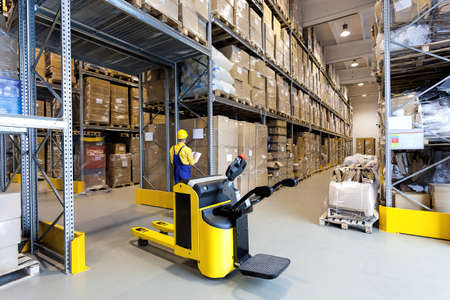 Huge metal stillage and yellow hand pallet truck in warehouse