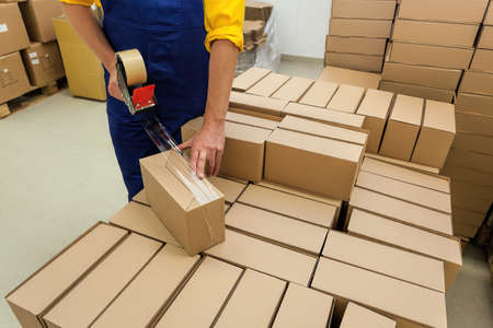 Warehouse worker packaging product for a customer Stock Photo