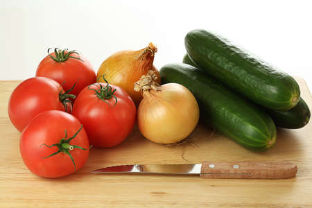 tomatos: Vegetables on the plank next to the knife ready to cut Stock Photo